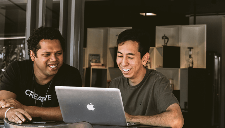 Friends Smiling at Laptop